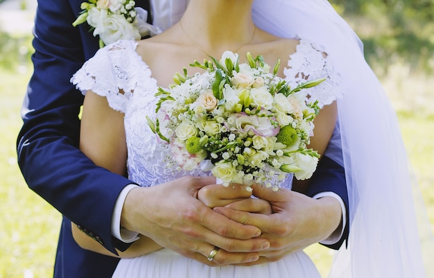 Bruid en bruidegom houden wit beige boeket samen in handen. zonnige, heldere foto. witte elegante jurk en diepblauw trouwpak.
