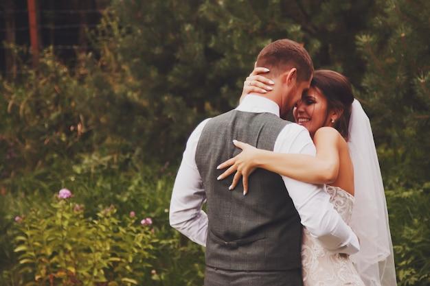 Bruid en bruidegom ierse stijl op trouwdag buiten wandelen in het dorpshuis van het land. bruidspaar gelukkige pasgetrouwde vrouw en man lopen in groen park of bebost. concept van huwelijksdag en getrouwd
