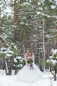 Bruid en bruidegom in beige gebreide truien in besneeuwde bossen. newlyweds raakt voorhoofd. winter bruiloft. kopieer ruimte