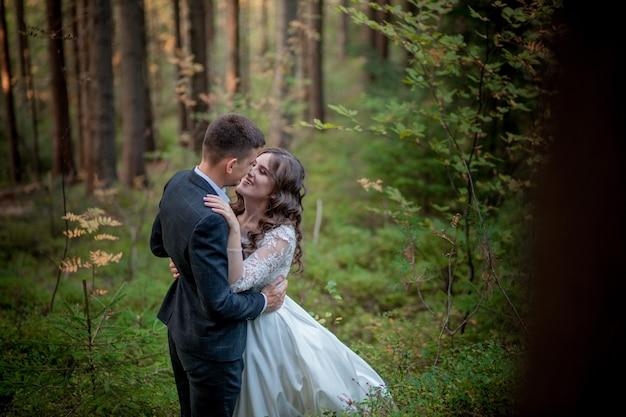 Bruid en bruidegom in bos op hun huwelijk, fotosessie.