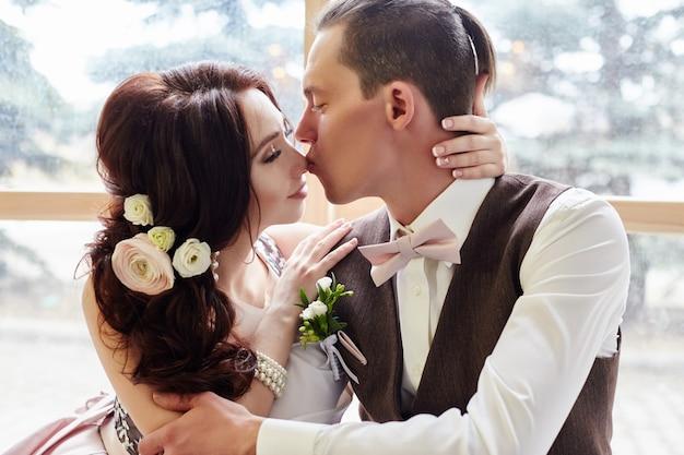 Bruid en bruidegom in de buurt van groot raam knuffelen voor bruiloft. liefde en tederheid in elke look. paar verliefd zoenen thuis. een man geeft een vrouw een boeket bloemen. rusland, sverdlovsk, 20 april 2018