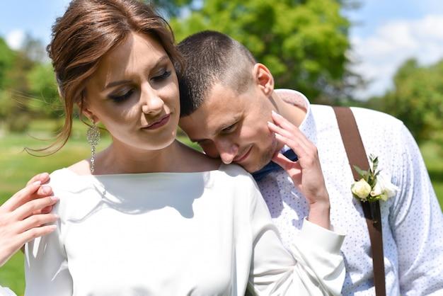 Bruid en bruidegom in een boeket lopen in een groen park