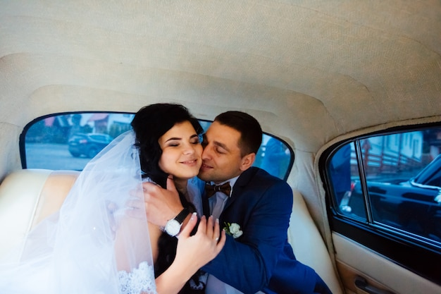 Bruid en bruidegom in een klassieke auto. zij zijn blij.