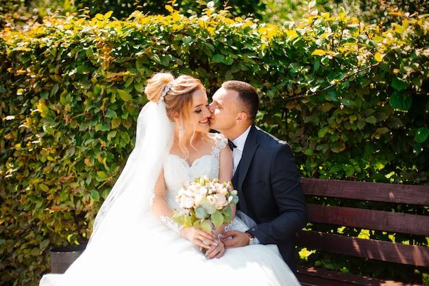 Bruid en bruidegom in een park zoenen. paar pasgetrouwden bruid en bruidegom op een bruiloft in de natuur groen bos kussen foto portret. bruidspaar