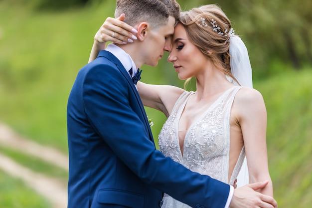 Bruid en bruidegom in een park zoenen. paar pasgetrouwden bruid en bruidegom op een bruiloft in de natuur groen bos kussen fotoportret. trouwkoppel