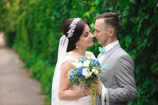 Bruid en bruidegom in een park zoenen. paar pasgetrouwden bruid en bruidegom op een bruiloft in de natuur groen bos