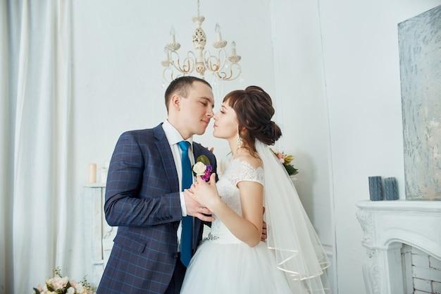 Bruid en bruidegom in huwelijkskleding omhelzen thuis. verliefde paar na een huwelijksceremonie