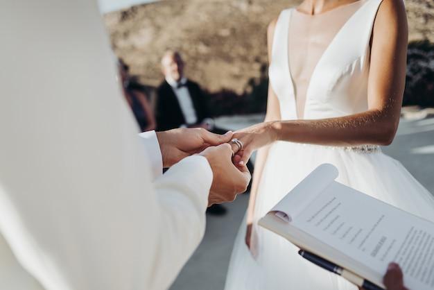 Bruid en bruidegom in lichte zomer kleding houden elkaar handen tijdens de ceremonie