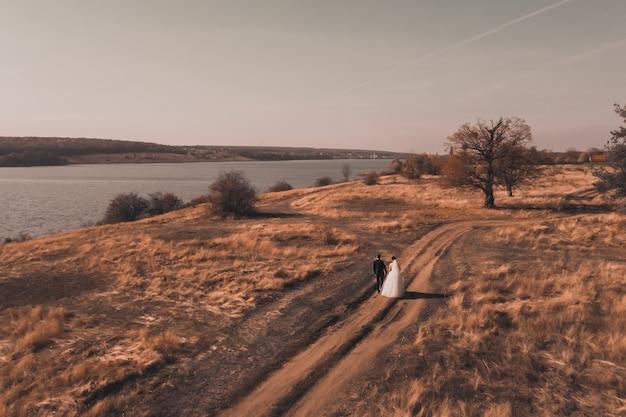 Bruid en bruidegom in trouwjurken lopen langs het herfst rode veld in de buurt van de rivier