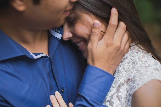 Bruid en bruidegom jonggehuwden kussen in het bos