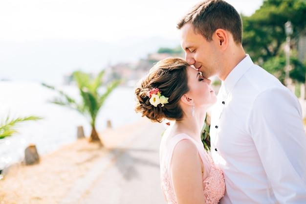 Bruid en bruidegom kijken elkaar aan en houden elkaars hand vast in perast.