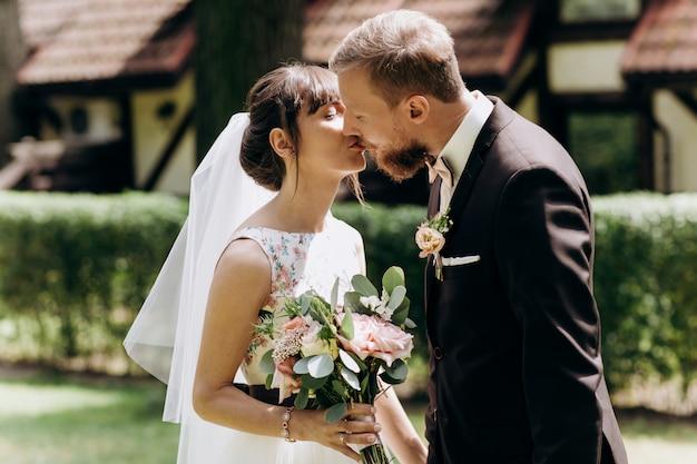Bruid en bruidegom kijken elkaar aan, knuffelen en zoenen