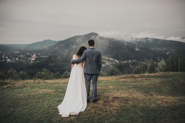 Bruid en bruidegom kijken naar het bos in de bergen in de mist