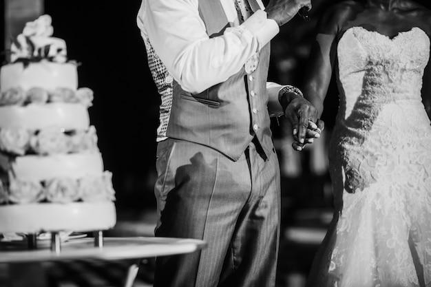 Bruid en bruidegom klaar om klassieke witte huwelijkscake te snijden
