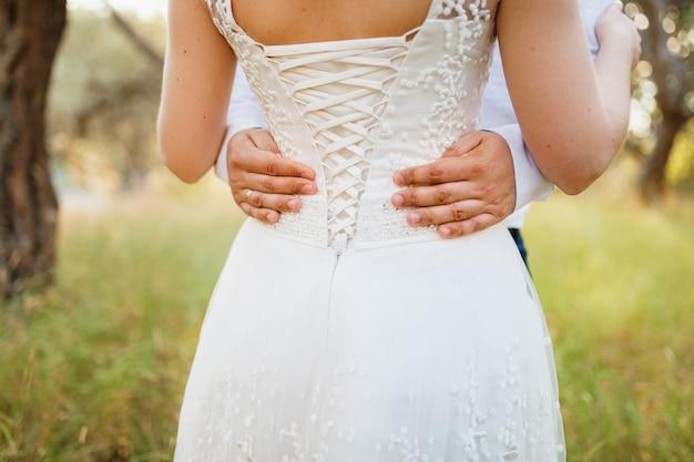 Bruid en bruidegom knuffel in een olijfgaard, bruidegom handen op de taille close-up van de bruid