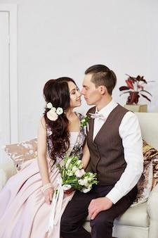Bruid en bruidegom knuffelen en poseren voor de bruiloft. liefde en tederheid in elke look. een verliefd stel knuffelt thuis. een man geeft een vrouw een boeket bloemen. rusland, sverdlovsk, 20 april 2018