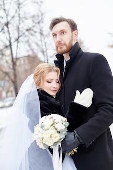 Bruid en bruidegom knuffelen en zoenen terwijl ze in de winter op straat staan. bruiloft, zachte omhelzing van man en vrouw. familie, de man en vrouw