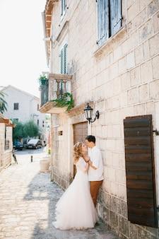 Bruid en bruidegom knuffelen in de buurt van een prachtig wit gebouw met balkons en houten luiken