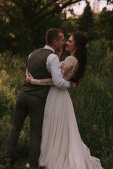 Bruid en bruidegom knuffelen in de zomer park
