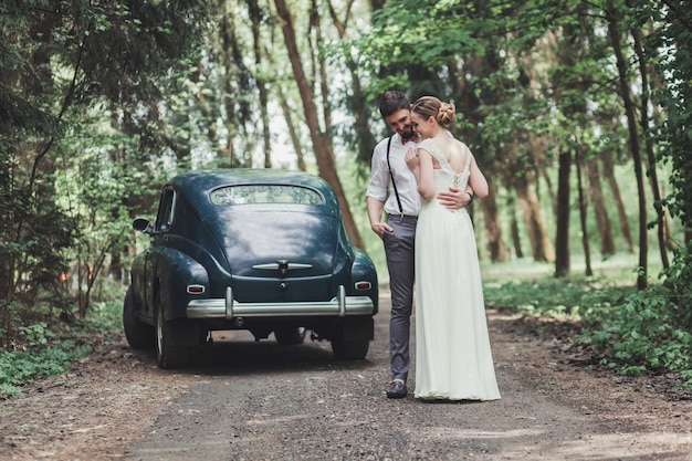 Bruid en bruidegom knuffelen in het bos