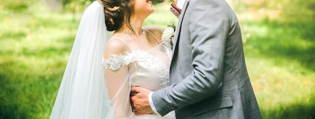 Bruid en bruidegom knuffelen in het park. gelukkig paar dat samen loopt. trouwdag foto. liefdesverhaal. mooie jurk met lange mouwen. kanten sluier. stijlvol rustiek boeket.