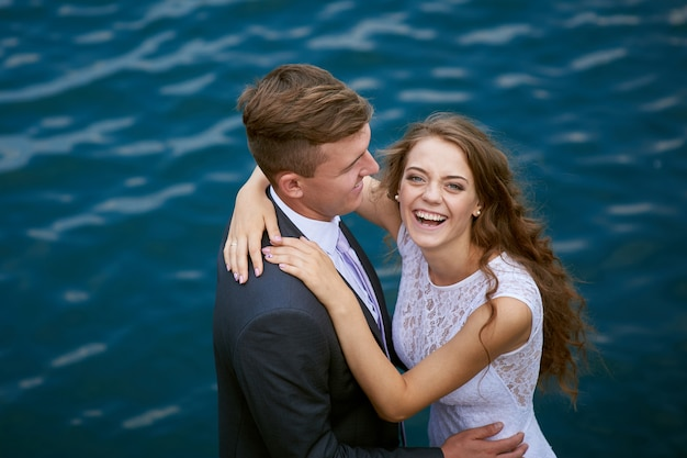Bruid en bruidegom knuffelen op de achtergrond van water