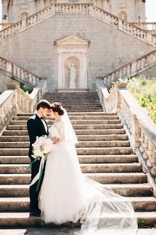 Bruid en bruidegom knuffelen op de trappen van de geboorte van de kerk van de heilige maagd maria in prcanj