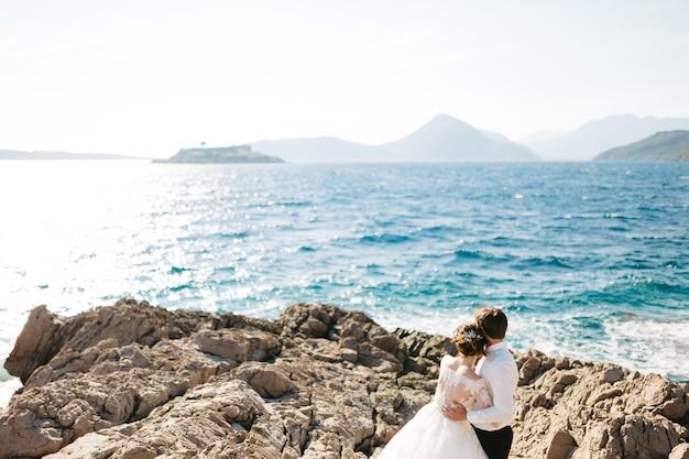 Bruid en bruidegom knuffelen op het rotsachtige strand van het mamula-eiland bij het fort van arza.