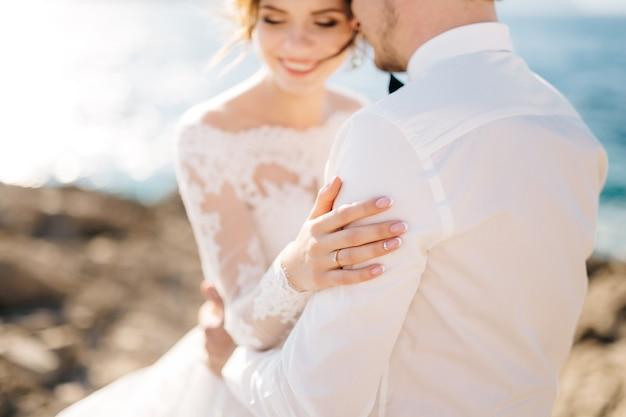 Bruid en bruidegom knuffelen op het rotsachtige strand van het mamula-eiland