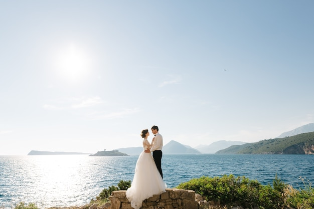 Bruid en bruidegom knuffelen op het strand van het mamula-eiland tegen de achtergrond van het fort arza.