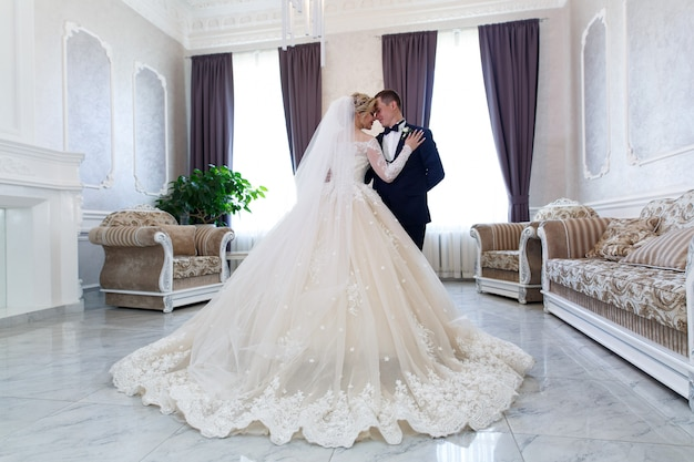 Bruid en bruidegom knuffelen zachtjes binnenshuis in een stijlvol interieur. wieden concept