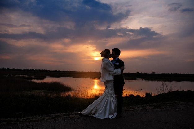Bruid en bruidegom kussen bij zonsondergang mooie romantische echtpaar