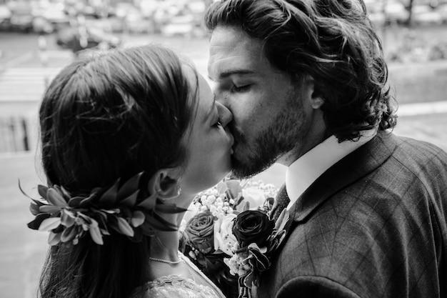 Bruid en bruidegom kussen buiten de kerk