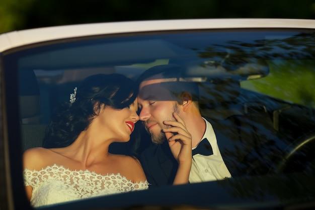 Bruid en bruidegom kussen in de auto
