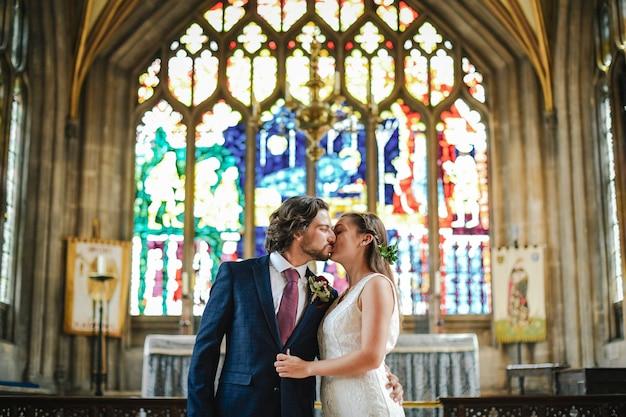 Bruid en bruidegom kussen op het altaar