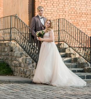 Bruid en bruidegom kussen, staande op de veranda van het huis