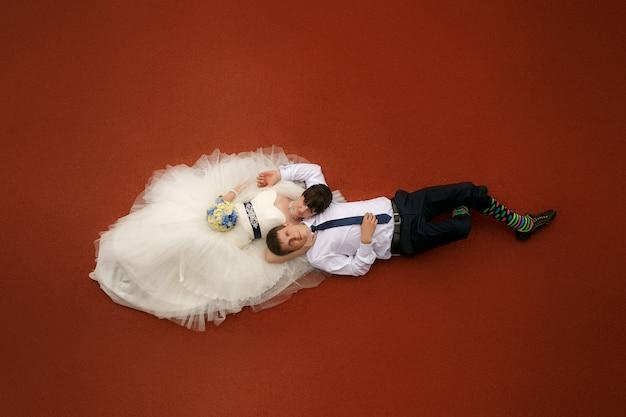 Bruid en bruidegom liggen op de rode vloer