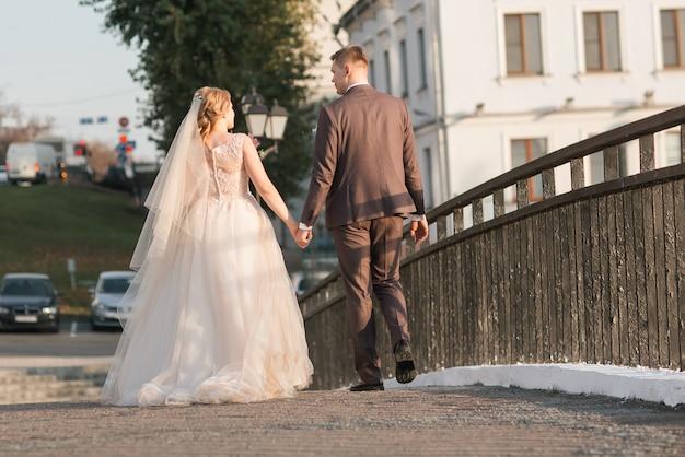 Bruid en bruidegom lopen door de straat van de stad