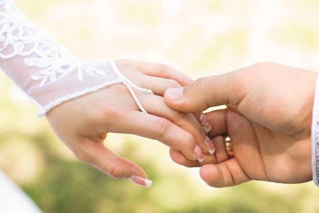 Bruid en bruidegom lopen hand in hand in het park