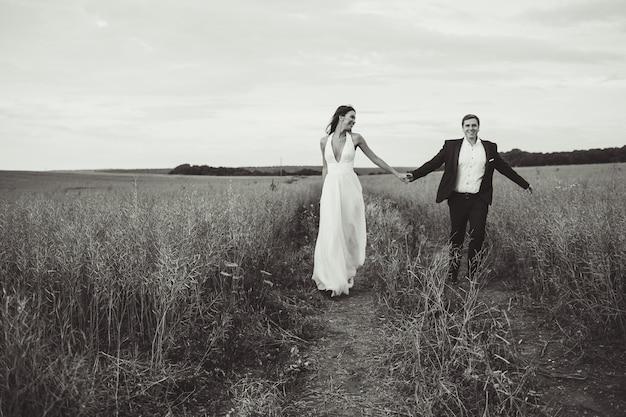 'bruid en bruidegom lopen in het veld'