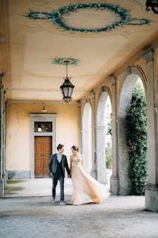 Bruid en bruidegom lopen langs het oude terras met zuilen