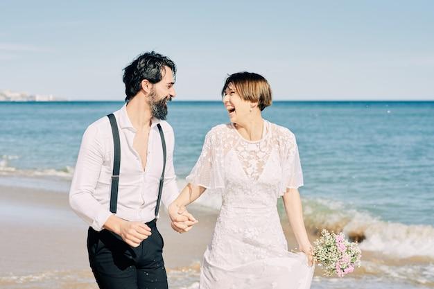 Bruid en bruidegom lopen langs het strand hand in hand en glimlachend gelukkig hun huwelijk vieren.