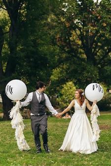 Bruid en bruidegom lopen met ballonnen met letters 'mr' en 'mrs' over het gazon in het park