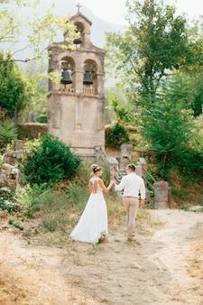 Bruid en bruidegom lopen naar de oude klokkentoren bij de kerk in prcanj hand in hand