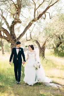 Bruid en bruidegom lopen samen in olijfgaard, kijken elkaar aan en hand in hand