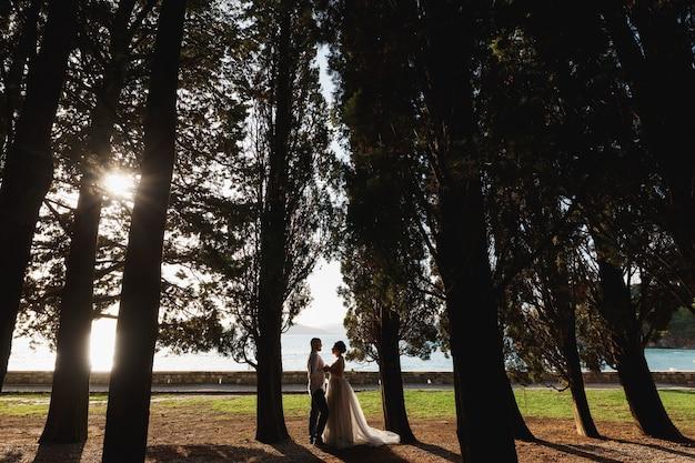 Bruid en bruidegom met een boeket staan omarmen en hand in hand