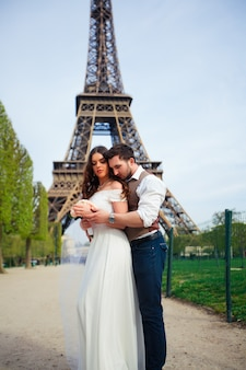 Bruid en bruidegom met een romantisch moment op hun trouwdag in parijs, tegenover de eiffeltoren
