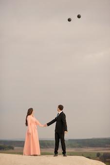 Bruid en bruidegom met grote helium ballonnen op bruiloft wandeling genieten van elkaar buiten met prachtig uitzicht bij zonsondergang