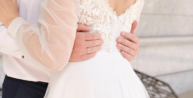 Bruid en bruidegom omarmd vanuit het oogpunt van de taille, geen hoofden op de foto