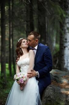 Bruid en bruidegom omarmen en kussen in het donkere bos in de zon. bruiloft in de natuur, portret van een paar verliefd in het park